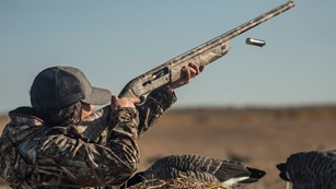 Woman Wingshooter In Camo Pointing Shotgun